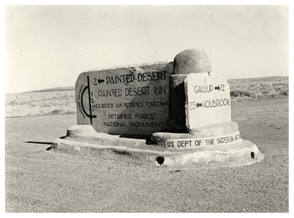 Park sign along Route 66 showing mileage and hours for Painted Desert Inn and mileage to Holbrook and Gallup, 1942