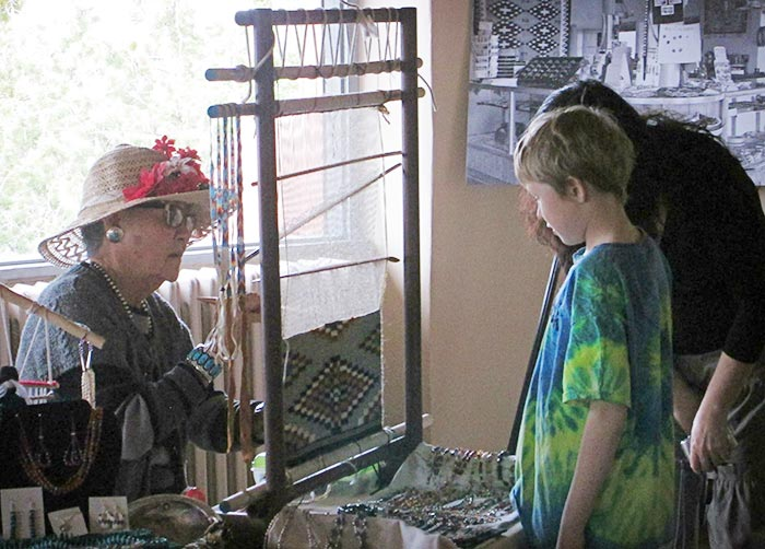 Alice Hawthorne demonstrates her traditional Navajo weaving skills for a visiting family.